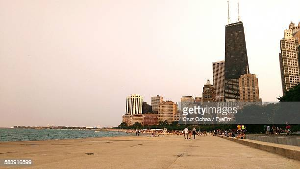 people walking on promenade amidst skyscrapers and sea against sky - waterfront stock pictures, royalty-free photos & images