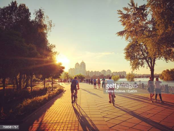 people walking on promenade in city at sunset - キエフ市 ストックフォトと画像