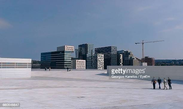 people walking on road against buildings - oslo stock pictures, royalty-free photos & images
