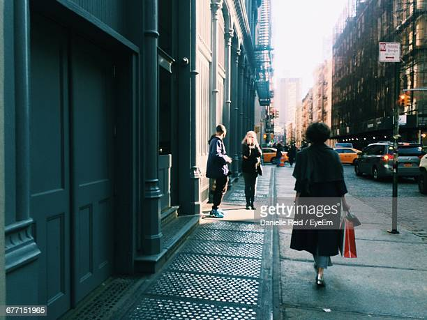 people walking on road along buildings - danielle reid stock pictures, royalty-free photos & images