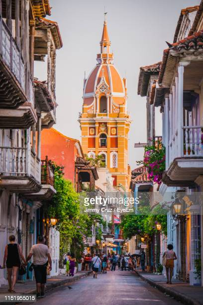 people walking on road amidst buildings in city against sky - cartagena colombia foto e immagini stock