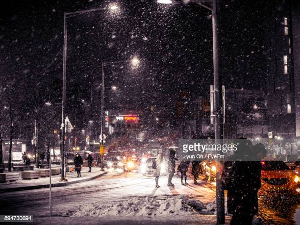 People Walking On Road During Winter At Night