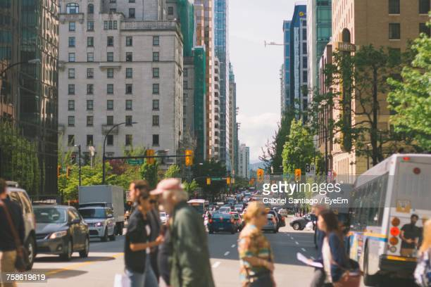 people walking on road in city - vancouver canada stock photos and pictures