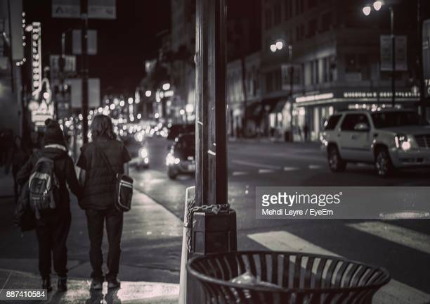 people walking on sidewalk in city at night - santa clarita stock pictures, royalty-free photos & images