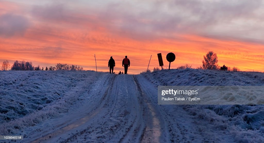 People Walking On Snow Covered Landscape Against Sky During Sunset : Stockfoto