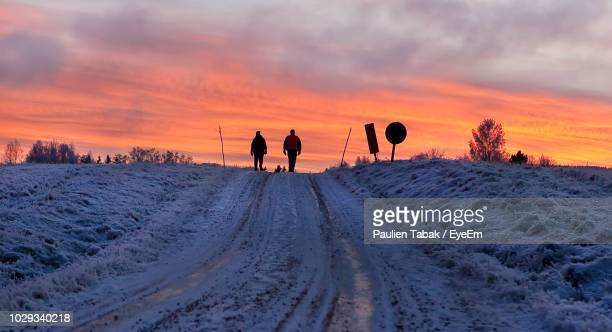 people walking on snow covered landscape against sky during sunset - paulien tabak 個照片及圖片檔