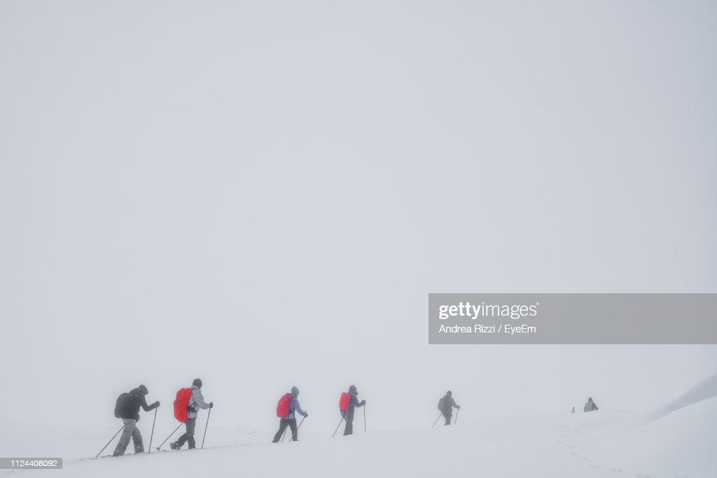 People Walking On Snow Covered Mountain During Extreme Weather : Foto stock