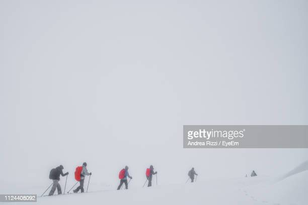 people walking on snow covered mountain during extreme weather - andrea rizzi stock pictures, royalty-free photos & images