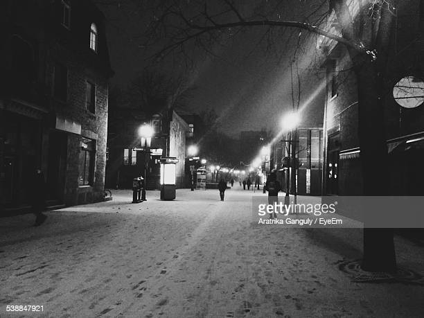 People Walking On Snow Covered Street In City At Night