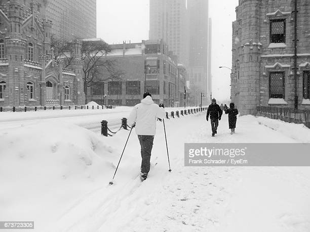 people walking on snow covered street - frank schrader stock pictures, royalty-free photos & images