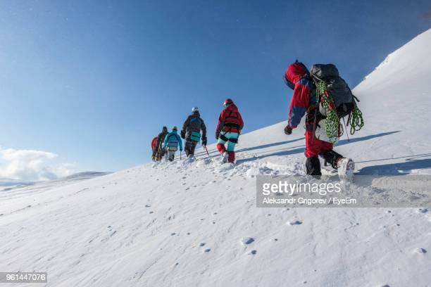 People Walking On Snowcapped Mountain Against Sky