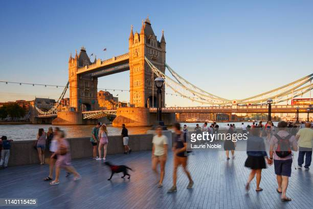 people walking on south bank in front of tower bridge at sunset, london, england, great britain - city stock pictures, royalty-free photos & images