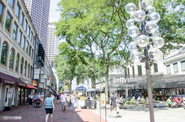 People walking on South Market Street besides the Boston Quincy Market during summer day