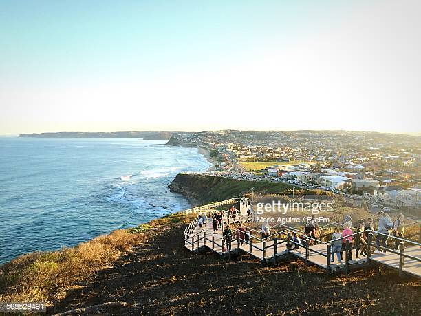 people walking on steps by sea against clear sky - newcastle new south wales stock pictures, royalty-free photos & images