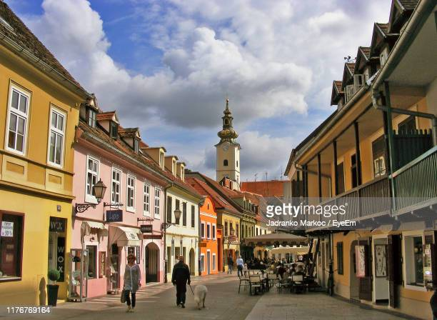 people walking on street amidst buildings in city against cloudy sky - zagreb stock pictures, royalty-free photos & images