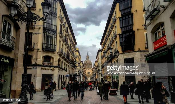 people walking on street amidst buildings in city - zaragoza province stock pictures, royalty-free photos & images