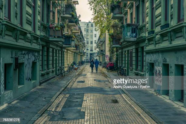 people walking on street amidst buildings - perspectiva espacial - fotografias e filmes do acervo