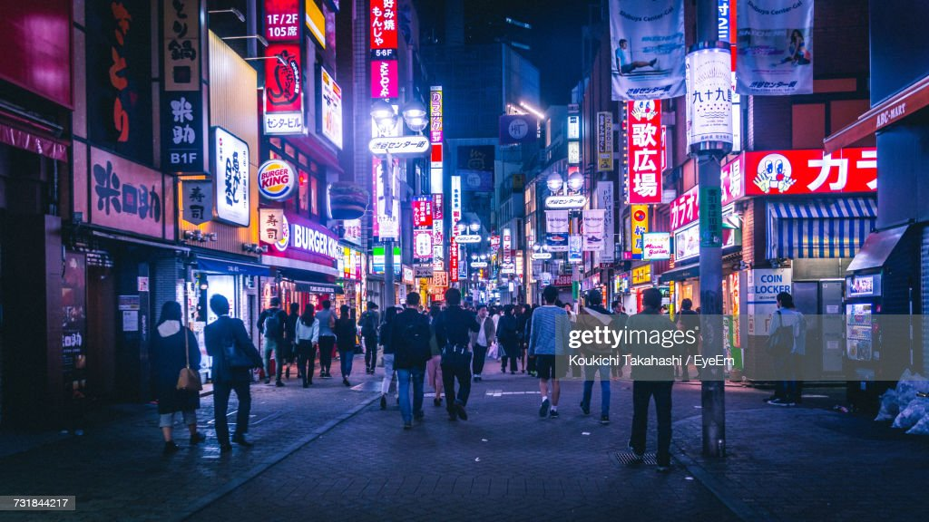 People Walking On Street Amidst Illuminated Buildings In City At Night : Stock Photo