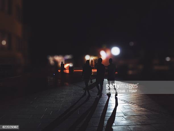 people walking on street at night - foco diferencial imagens e fotografias de stock