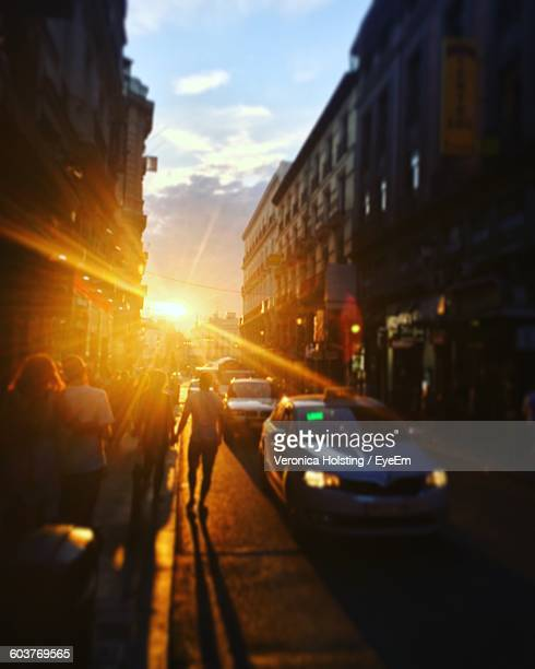 People Walking On Street By Cars Amidst Buildings During Sunset