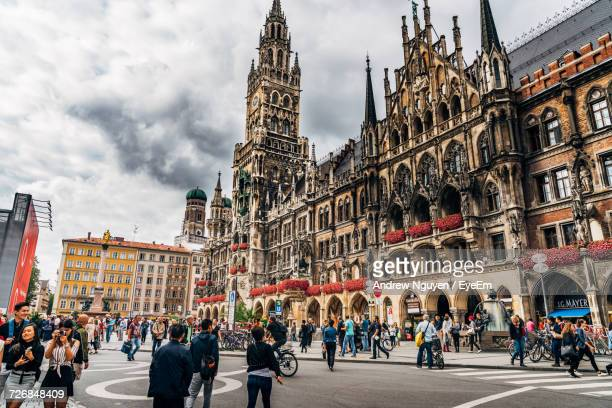 people walking on street by new town hall at marienplatz - münchen stock-fotos und bilder
