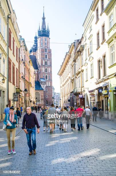 People walking on street close to Square Market with St. Mary's Basilica behind during summer day.