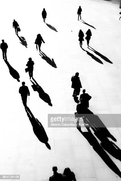 people walking on street - shadow stock pictures, royalty-free photos & images
