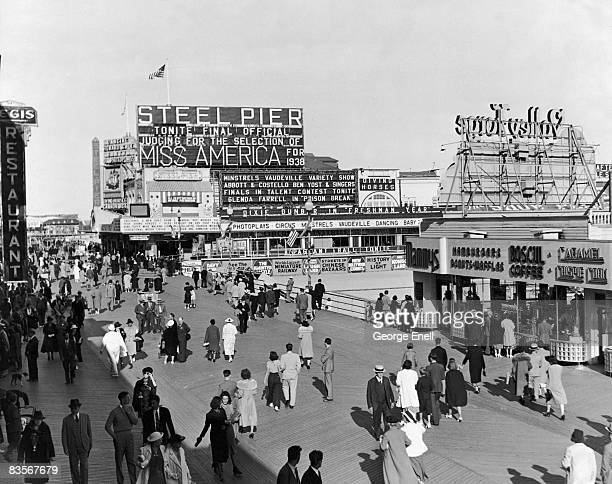 People walking on the boardwalk at Atlantic City New Jersey 1938 A billboard announces the final judging for the selection of Miss America for 1938