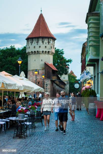 people walking on the narrow medieval streets of sibiu, romania - sibiu stock photos and pictures