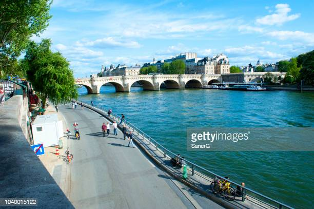 people walking on the quay along the seine river in paris - quayside stock pictures, royalty-free photos & images