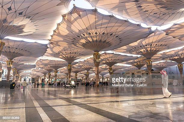 people walking on tiled floor below sunshades of al-masjid an-nabawi - mosque stock pictures, royalty-free photos & images