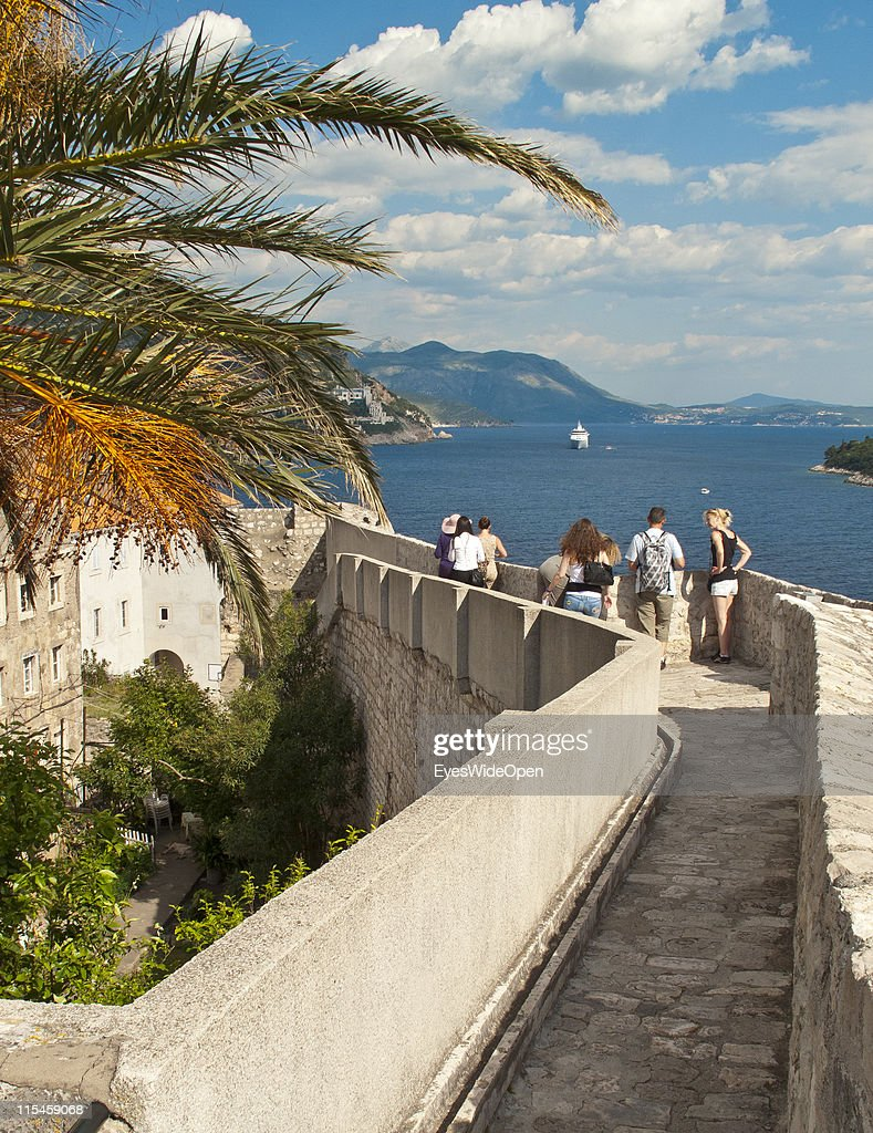 People walking on top of the 1,9 km long city wall of the UNESCO World Heritage Site city of Dubrovnik on the Dalmatian coast of the Adriatic Sea on May 13, 2011 in Dubrovnik, Croatia. The old town is called the Pearl of the Adriatic.