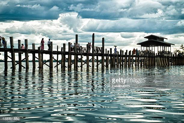 people walking on u bein's bridge - luisapuccini stock-fotos und bilder
