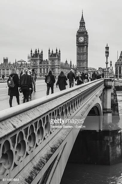 people walking on westminster bridge by big ben against sky in city - westminster bridge stock pictures, royalty-free photos & images