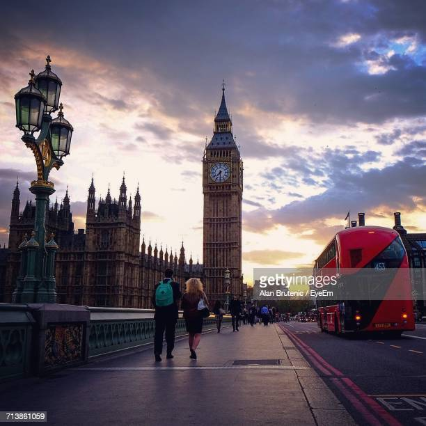People Walking On Westminster Bridge By Big Ben During Sunset In City