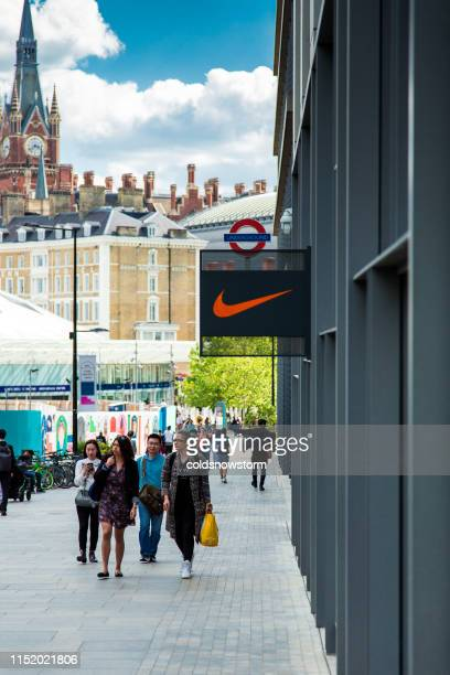 people walking outside nike town store at king's cross, london, uk - designer label stock pictures, royalty-free photos & images