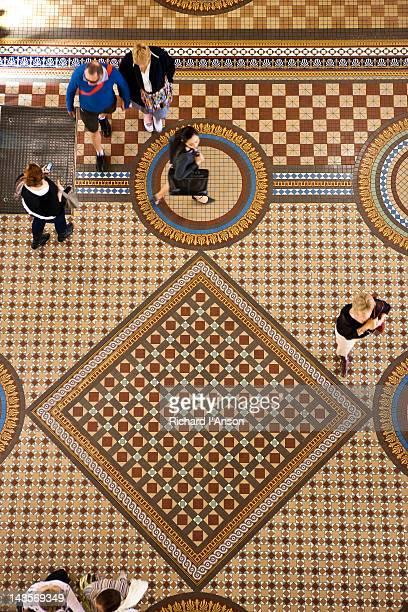 people walking over tiled floor in queen victoria building. - queen victoria stock pictures, royalty-free photos & images