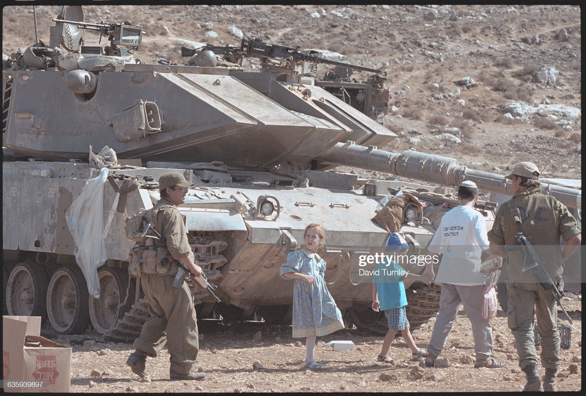 https://media.gettyimages.com/photos/people-walking-past-a-tank-picture-id635939897?s=2048x2048