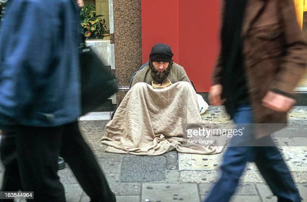 People walking past homeless man begging on Oxford Street, London, England, UK