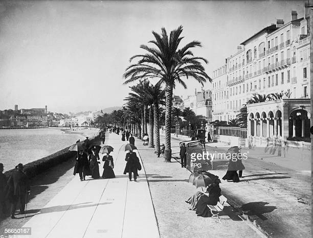 People walking past palm trees along the Boulevard de la Croisette on the seafront at Cannes early 1900s