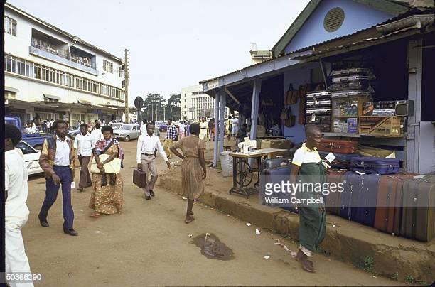 People walking past store selling luggage