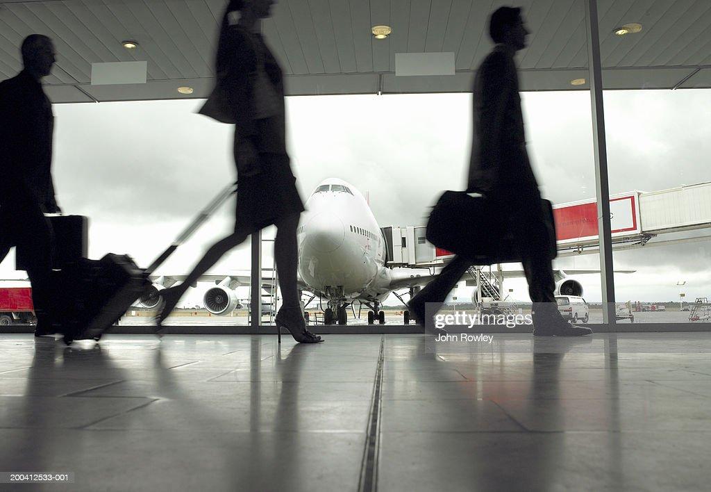 People walking through airport, silhouette (focus on aeroplane) : Stock Photo