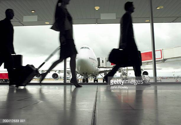people walking through airport, silhouette (focus on aeroplane) - geschäftsreise stock-fotos und bilder