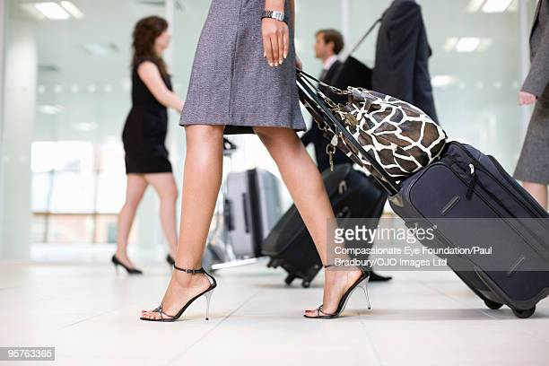 people walking through an airport with luggage - high heels stock pictures, royalty-free photos & images