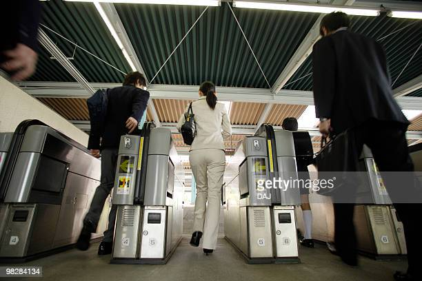 People walking through automatic ticket wicket at station, blurred motion