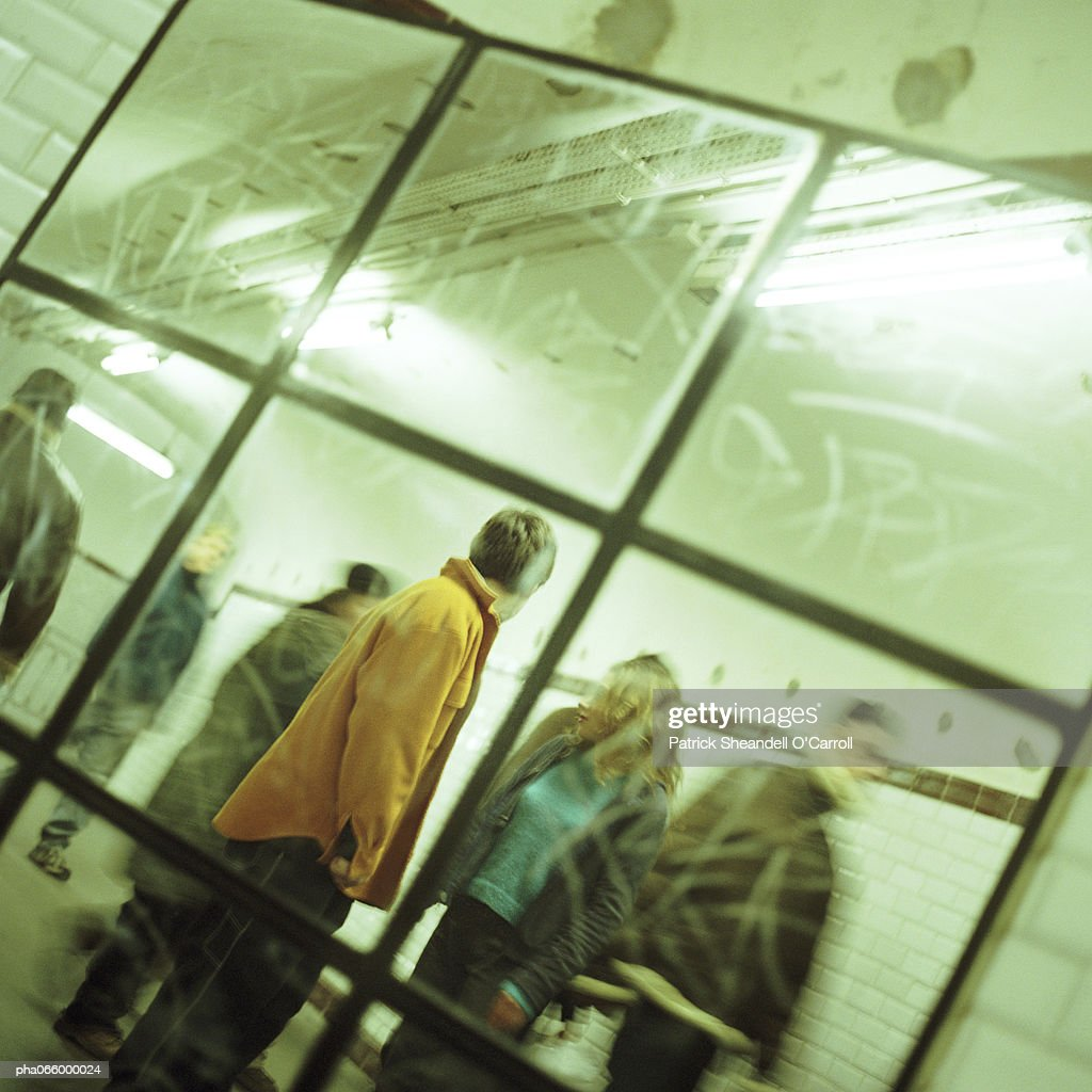 People walking through corridor, viewed through mirror. : Stockfoto