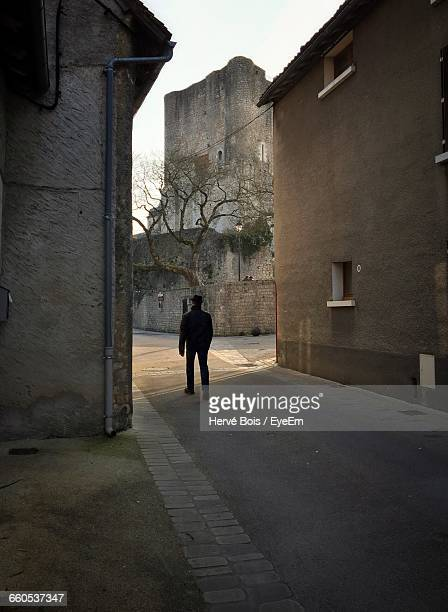people walking through narrow alley along buildings - chauvigny stock pictures, royalty-free photos & images