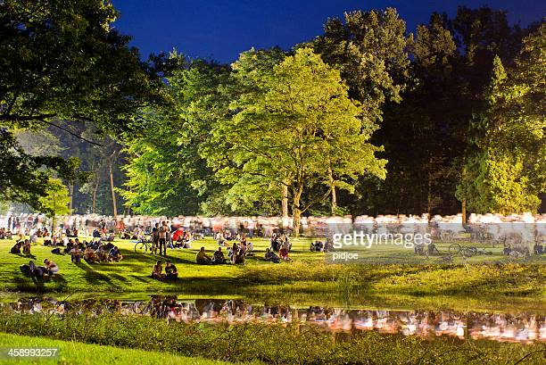 people walking through park after concert at night - gelderland stock pictures, royalty-free photos & images