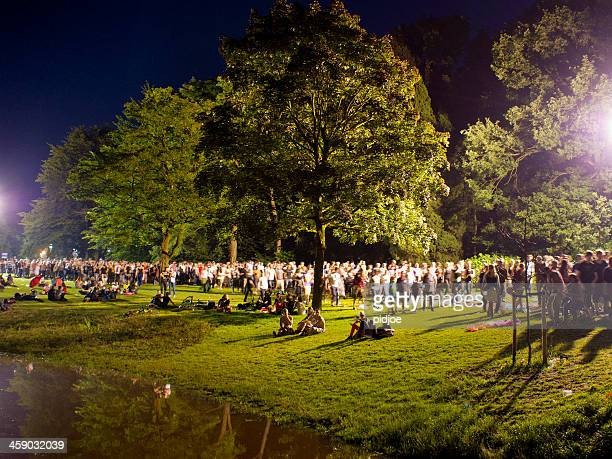 people walking through park after concert at night - nijmegen stock pictures, royalty-free photos & images