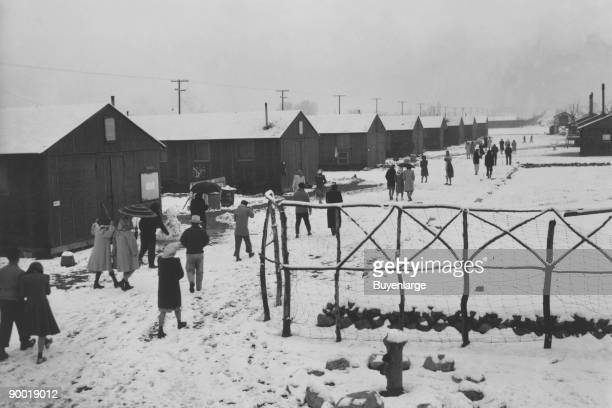 People walking through relocation center in snow past hand made wood fence Ansel Easton Adams was an American photographer best known for his...